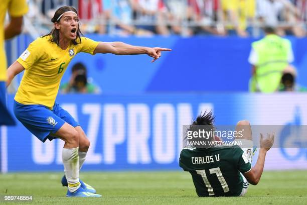 Brazil's defender Filipe Luis reacts as Mexico's forward Carlos Vela falls during the Russia 2018 World Cup round of 16 football match between Brazil...