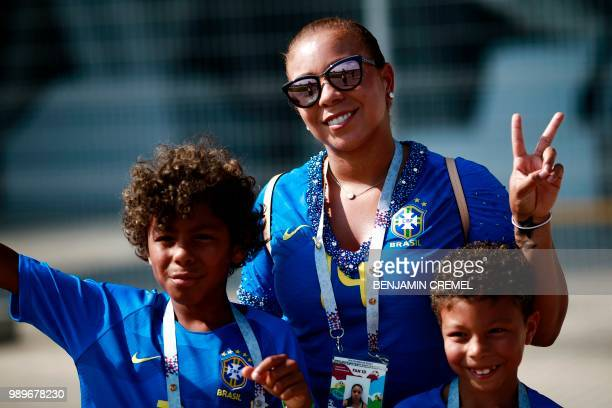 Brazil's defender Thiago Silva's wife Isabele da Silva poses with her children before the Russia 2018 World Cup round of 16 football match between...