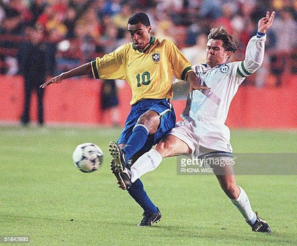 Brazil's Denilson de Oliveira tries to control an offensive effort by an unidentified Guatemalan player during first half action in their game of the...