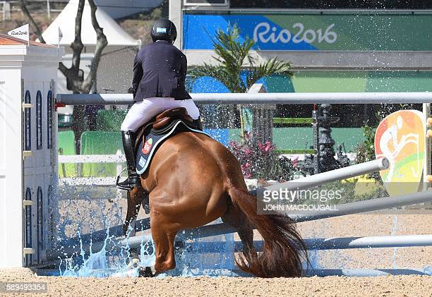 Brazil's Eduardo Menezes on Quintol hits an obstacle during the Equestrian's Show Jumping first qualifier event of the 2016 Rio Olympic Games at the...