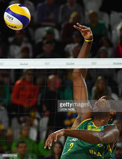 Brazil's Evandro Goncalves Oliveira Junior spikes the ball during the men's beach volleyball qualifying match between Brazil and Latvia at the Beach...