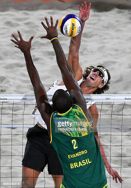 Brazil's Evandro Goncalves Oliveira Junior tries to block the ball during the men's beach volleyball qualifying match between Brazil and Latvia at...