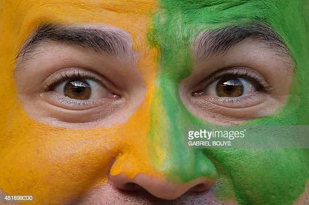 Brazil's fan cheers before the quarterfinal football match between Brazil and Colombia at the Castelao Stadium in Fortaleza during the 2014 FIFA...