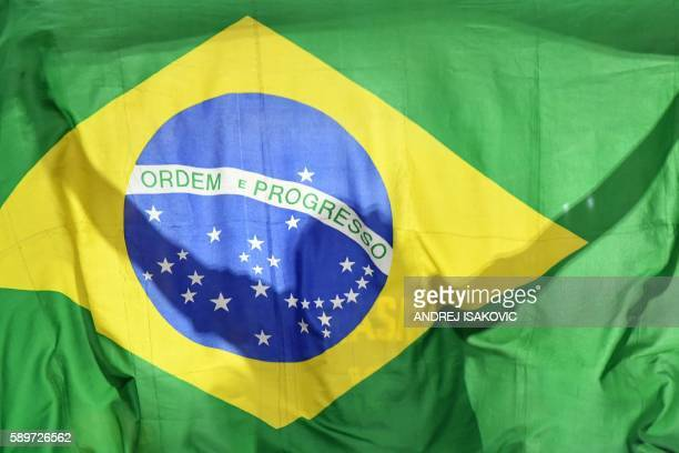 A Brazil's fan waves their national flag during a Men's round Group B basketball match between Nigeria and Brazil at the Carioca Arena 1 in Rio de...