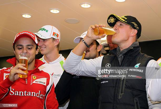 Brazil's Felipe Massa of Ferrari and Germany's Michael Schumacher of Mercedes GP drinks as they celebrate the 20th annivesary of Schumacher's F1...