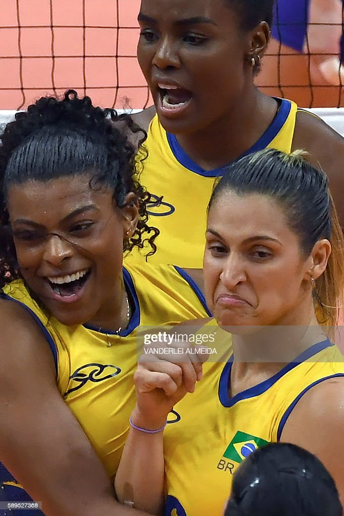 Brazil's Fernanda Rodrigues (L) , Brazil's Danielle Lins (R) and Brazil's Fabiana Claudino (top) celebrate during the women's qualifying volleyball match between Brazil and Russia at the Maracanazinho stadium in Rio de Janeiro on August 14, 2016, during the Rio 2016 Olympic Games. / AFP / VANDERLEI