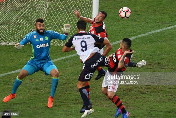 Brazil's Flamengo goalkeeper Alex Muralha and teammates Rever and Para vie for the ball with Argentina's San Lorenzo Nicolas Blandi during their...
