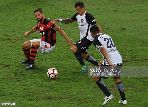 Brazil's Flamengo player Diego Ribas vies for the ball against Argentina's San Lorenzo Franco Mussis and Nestor Ortigoza during their Libertadores...