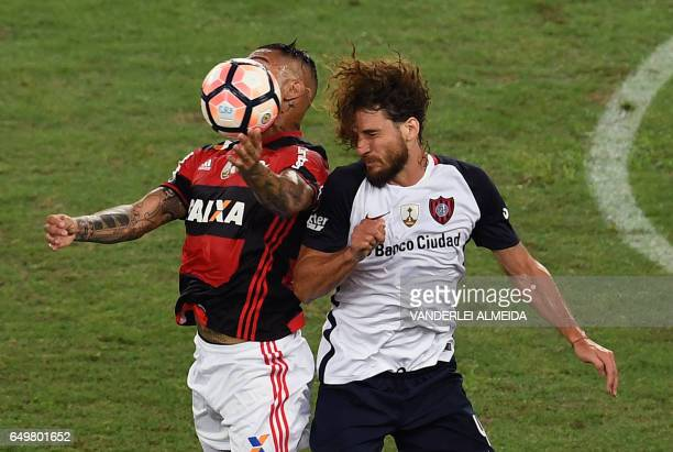 Brazil's Flamengo player Paolo Guerrero jumps for the ball with Argentina's San Lorenzo Fabricio Coloccini during their Libertadores Cup football...