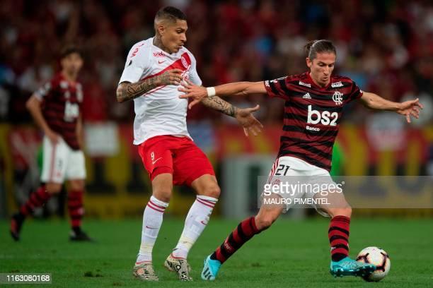 Brazil's Flamengo team player Filipe Luis vies for the ball with Brazil's Internacional player Paolo Guerrero during a 2019 Copa Libertadores...