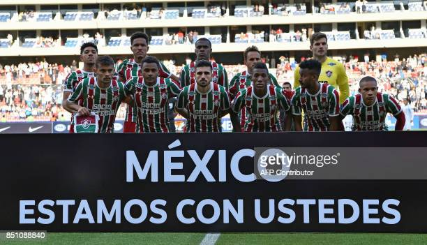 Brazil's Fluminense players pose behind a banner reading 'Mexico we are with you' before their 2017 Sudamericana Cup football match against Ecuador's...