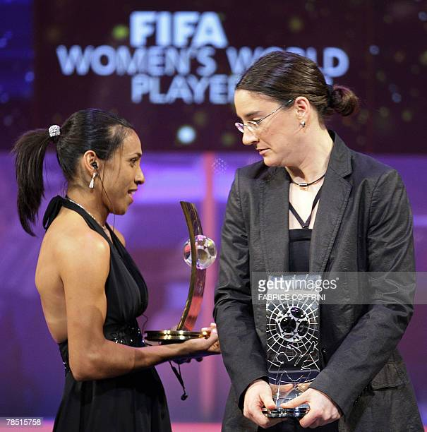 Brazil's football player Marta holding the trophy of FIFA women's Player of the Year walks behind Germany's football player Birgit Prinz during the...