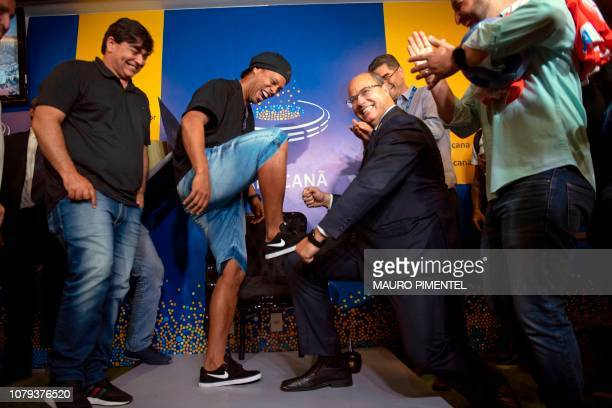 Brazil's football player Ronaldinho Gaucho poses for pictures while Rio de Janeiro's Governor Wilson Witzel 'waxes' his shoes during a ceremony to...