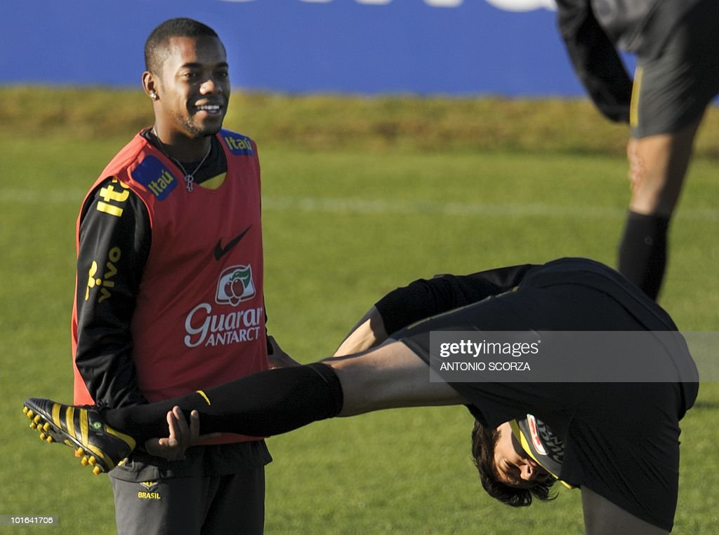 Brazil's football team striker Kaka (R) stretches with teammate Robinho during a training session at the Randburg High School on June 5, 2010 in Johannesburg. The team is preparing to compete in the 2010 World Cup in South Africa. AFP PHOTO / ANTONIO