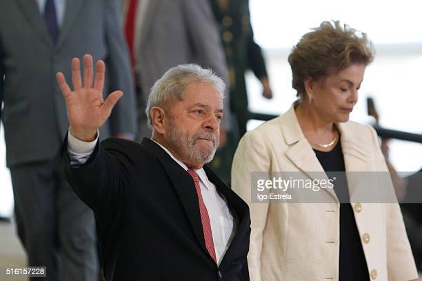 Brazil's former president, Luiz Inacio Lula da Silva walks with President Dilma Rousseff as he is sworn in as the new chief of staff in the Planalto...