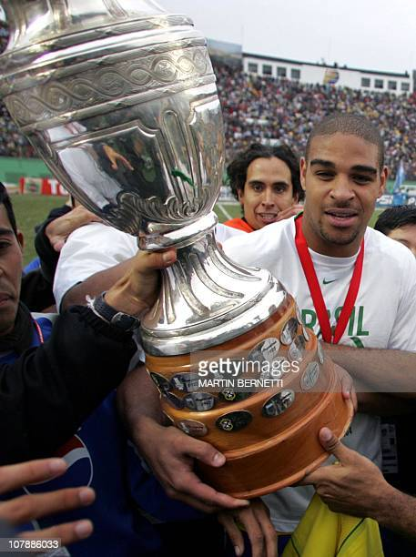 Brazil's forward and striker Adriano Ribeiro holds the Copa America 2004 trophy, 25 July 2004, after defeating Argentina in the final match at the...