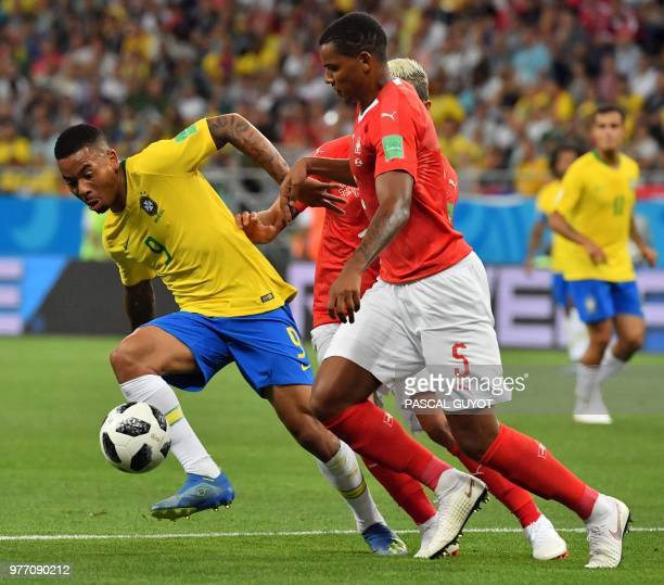 Brazil's forward Gabriel Jesus Switzerland's midfielder Valon Behrami and Switzerland's defender Manuel Akanji compete for the ball during the Russia...