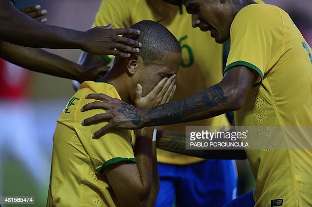 Brazil's forward Marcos Guilherme is congratulated by teammates after scoring against Chile during a South American U-20 football match at Domingo...