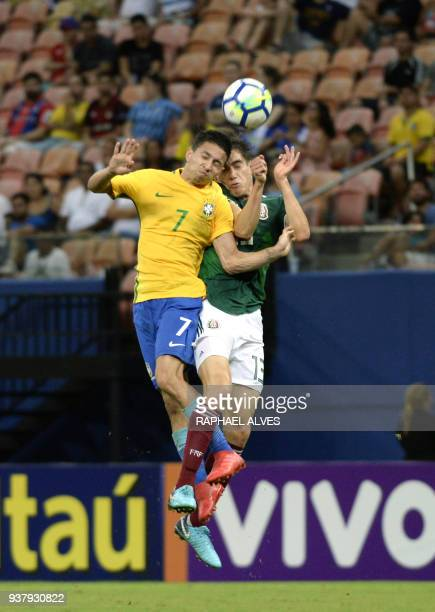 Brazil's forward Mauro Junior jumps for the ball with Mexico's defender Edgar Lopez during the international friendly Under20 football match in Arena...