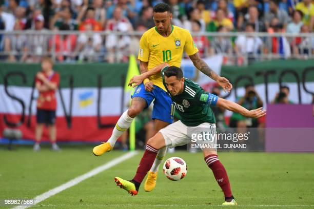 Brazil's forward Neymar and Mexico's midfielder Andres Guardado vie for the ball during the Russia 2018 World Cup round of 16 football match between...