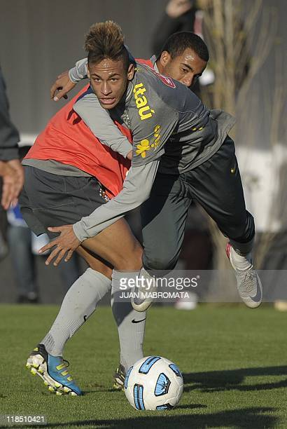 Brazil's forward Neymar and midfielder Lucas vie during a training session of the national football team near Campana some 70 Km of Buenos Aires on...