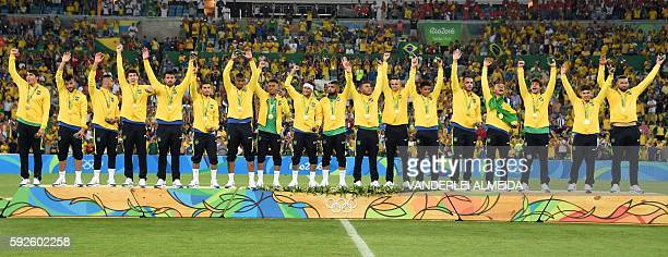 Brazil's forward Neymar and teammates celebrate on the podium during the medal presentation following the Rio 2016 Olympic Games men's football gold...