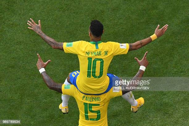 TOPSHOT Brazil's forward Neymar celebrates scoring the opening goal on shoulders of Brazil's midfielder Paulinho during the Russia 2018 World Cup...