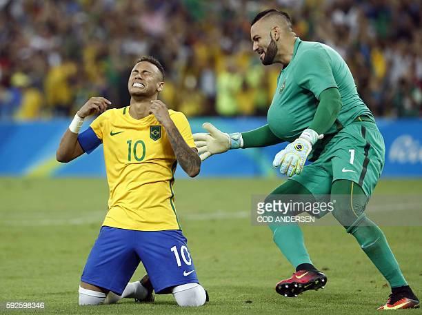 Brazil's forward Neymar celebrates scoring the winning goal with Brazil's goalkeeper Weverton Pereira da Silva during the penalty shoot-out of the...