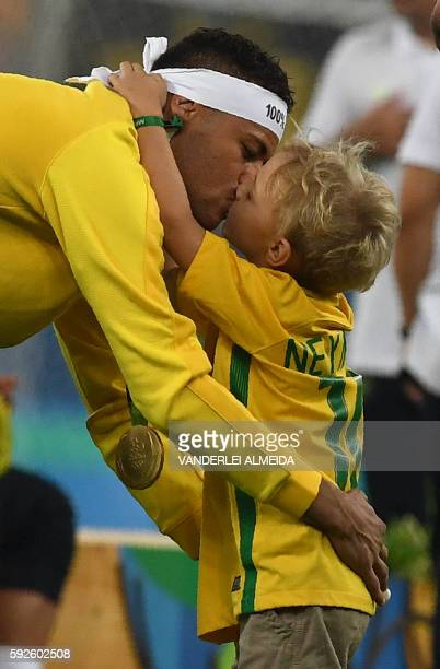 Brazil's forward Neymar celebrates with his son after the Rio 2016 Olympic Games men's football gold medal match between Brazil and Germany at the...