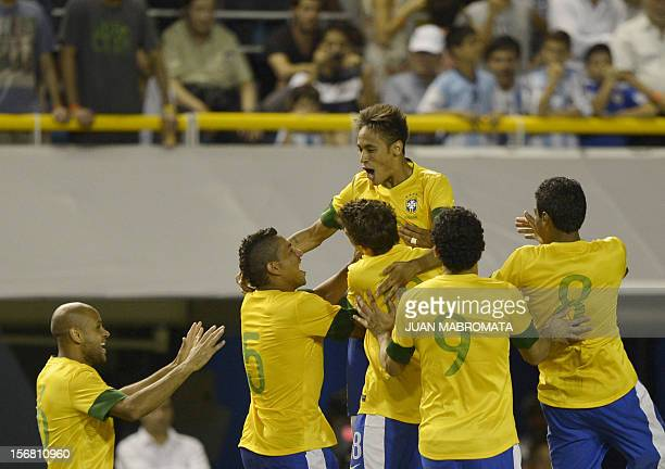 Brazil's forward Neymar celebrates with teammates after scoring the last penalty shoot against Argentina during a friendly football match at...