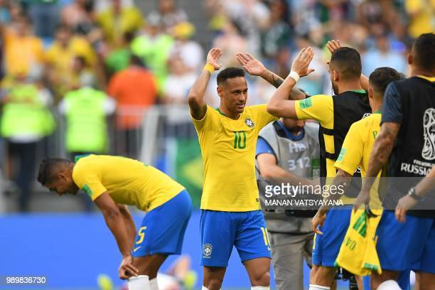 Brazil's forward Neymar celebrates with teammates after winning at the end of the Russia 2018 World Cup round of 16 football match between Brazil and...