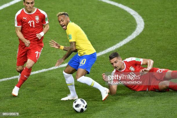 TOPSHOT Brazil's forward Neymar challenges Serbia's midfielder Sergej MilinkovicSavic and Serbia's forward Filip Kostic during the Russia 2018 World...