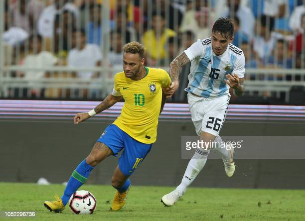 Brazil's forward Neymar drives the ball past Argentina's defender Renzo Saravia during the friendly football match Brazil vs Argentina at the King...