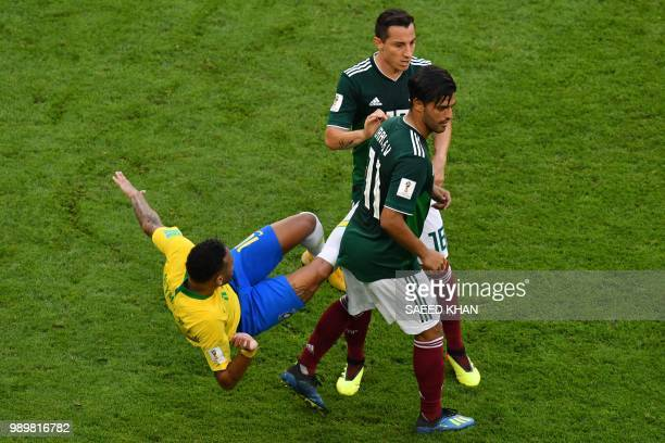 Brazil's forward Neymar falls after a challenge from Mexico's midfielder Andres Guardado and Mexico's forward Carlos Vela during the Russia 2018...