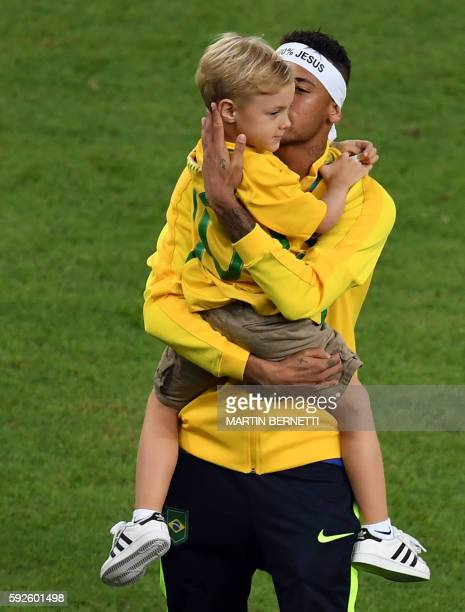 Brazil's forward Neymar holds his son as he celebrates after the Rio 2016 Olympic Games men's football gold medal match between Brazil and Germany at...