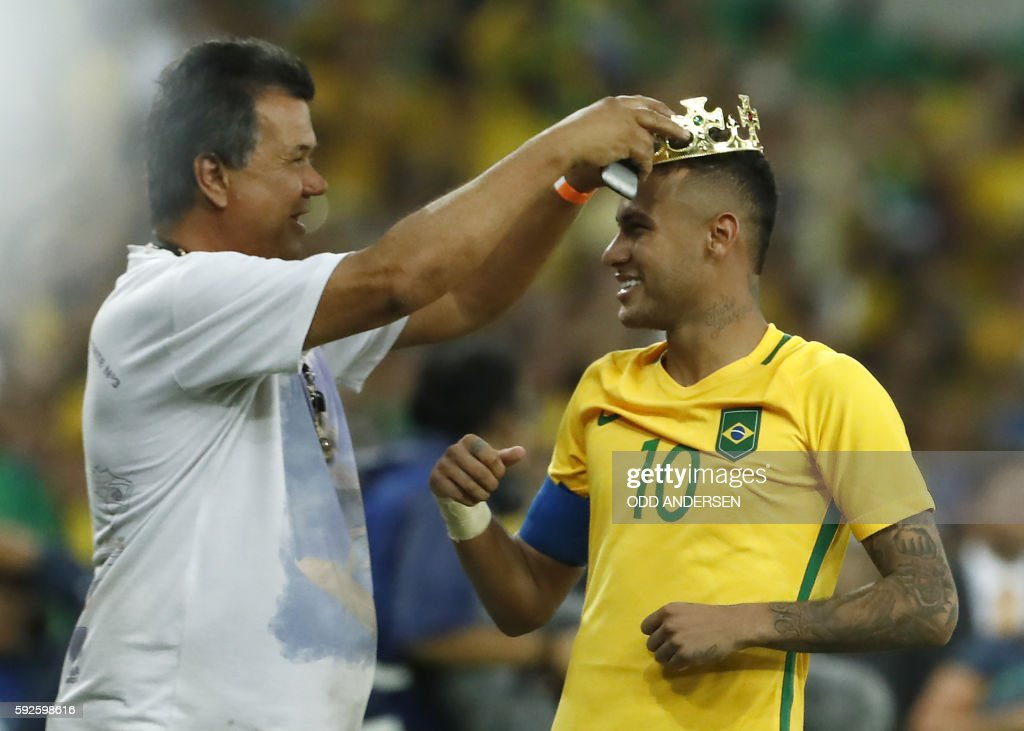 TOPSHOT - Brazil's forward Neymar (R) is given a crown after scoring the winning goal during the penalty shoot-out of the Rio 2016 Olympic Games men's football gold medal match between Brazil and Germany at the Maracana stadium in Rio de Janeiro on August 20, 2016. / AFP PHOTO / Odd Andersen