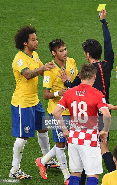 Brazil's forward Neymar is restrained by teammate Brazil's defender Marcelo as Japanese referee Yuichi Nishimura issues a yellow card during a Group...
