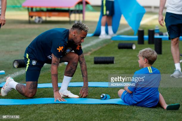 Brazil's forward Neymar jokes with his son Davi Lucca during a training session at the Yug-Sport Stadium in Sochi on June 29, 2018 during the Russia...