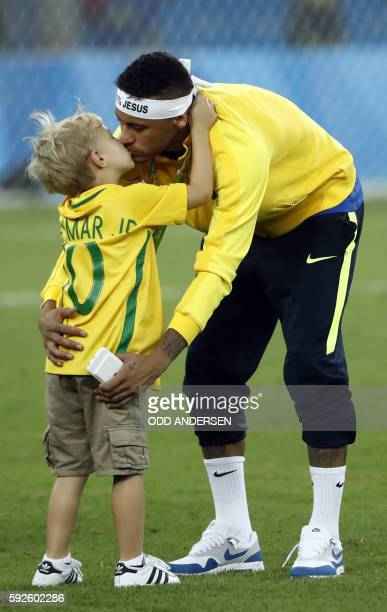 Brazil's forward Neymar kisses his son after the Rio 2016 Olympic Games men's football gold medal match between Brazil and Germany at the Maracana...