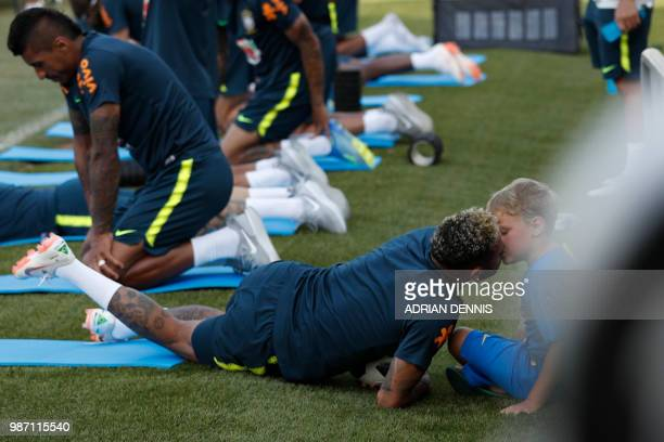 Brazil's forward Neymar kisses his son Davi Lucca during a training session at the Yug-Sport Stadium in Sochi on June 29, 2018 during the Russia 2018...