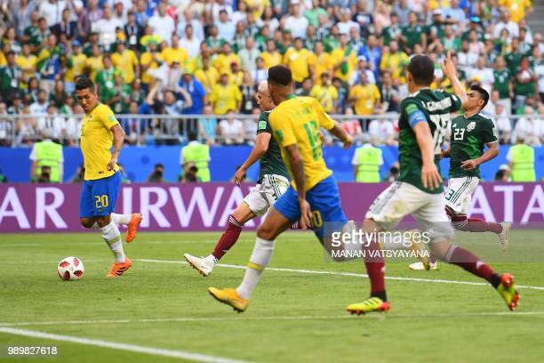 Brazil's forward Neymar passes the ball to Brazil's forward Roberto Firmino who shoots and scores a goal during the Russia 2018 World Cup round of 16...