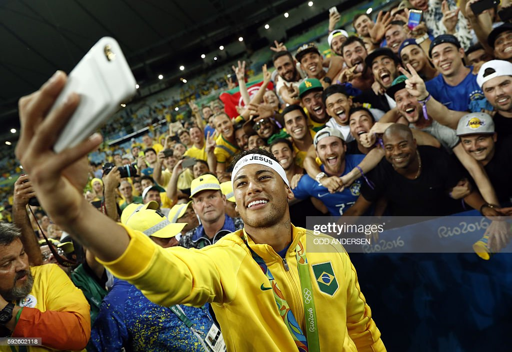 TOPSHOT - Brazil's forward Neymar poses for a selfie with fans as they celebrate after the Rio 2016 Olympic Games men's football gold medal match between Brazil and Germany at the Maracana stadium in Rio de Janeiro on August 20, 2016. / AFP / Odd ANDERSEN