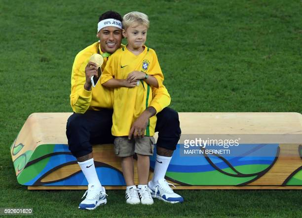 Brazil's forward Neymar poses with his son after the Rio 2016 Olympic Games men's football gold medal match between Brazil and Germany at the...