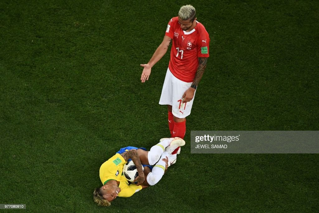 TOPSHOT - Brazil's forward Neymar (L) reacts after a tackle by Switzerland's midfielder Valon Behrami during the Russia 2018 World Cup Group E football match between Brazil and Switzerland at the Rostov Arena in Rostov-On-Don on June 17, 2018. (Photo by Jewel SAMAD / AFP) / RESTRICTED