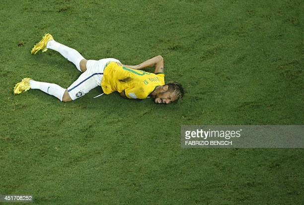 Brazil's forward Neymar reacts on the ground after being injured following a foul by Colombia's defender Juan Camilo Zuniga during the quarterfinal...