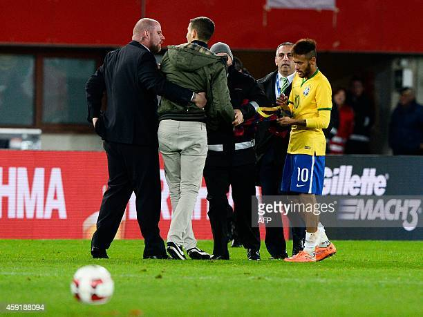Brazil's forward Neymar signs a shirt for a fan before stewards take him away during a friendly football match Austria vs Brazil at the Ernst Happel...