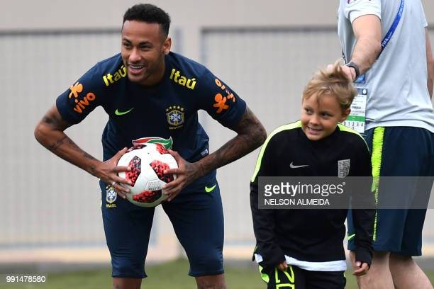 Brazil's forward Neymar smiles past his son Davi Lucca during a training session at Yug Sport Stadium in Sochi on July 4 during the Russia 2018 World...