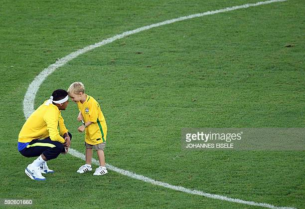 Brazil's forward Neymar speaks with his son after the Rio 2016 Olympic Games men's football gold medal match between Brazil and Germany at the...