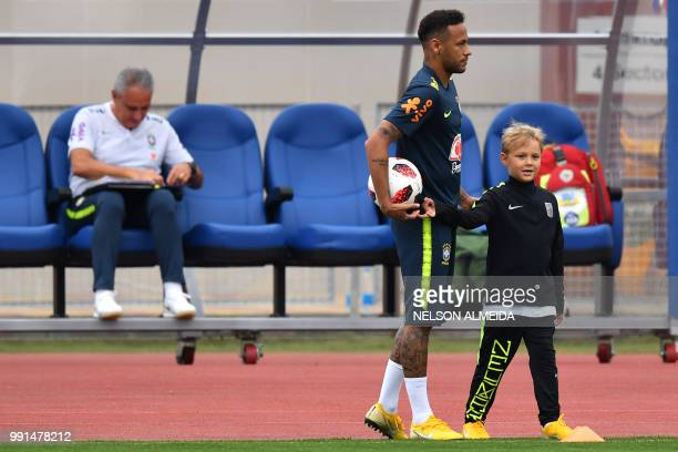 Brazil's forward Neymar stands past his son Davi Lucca during a training session at Yug Sport Stadium, in Sochi, on July 4 during the Russia 2018...