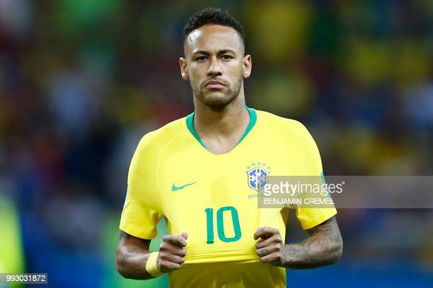 TOPSHOT Brazil's forward Neymar stretches his jersey during the Russia 2018 World Cup quarterfinal football match between Brazil and Belgium at the...